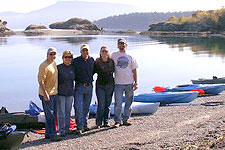 A small group of kayakers lands on a pebble beach on Sucia Island