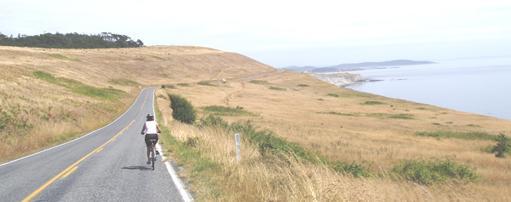 Bicycling on Cattle Point Road, San Juan Island. Washington state.