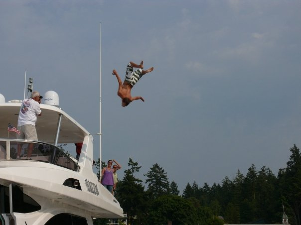 Fun in the summera a man flips off a luxury yacht into the water at Roche Harbor, San Juan Island.