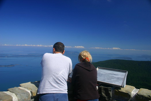 A couple enjoys the panoramic view offered from the watchtower atop Mont Constitution on Orcas Island.